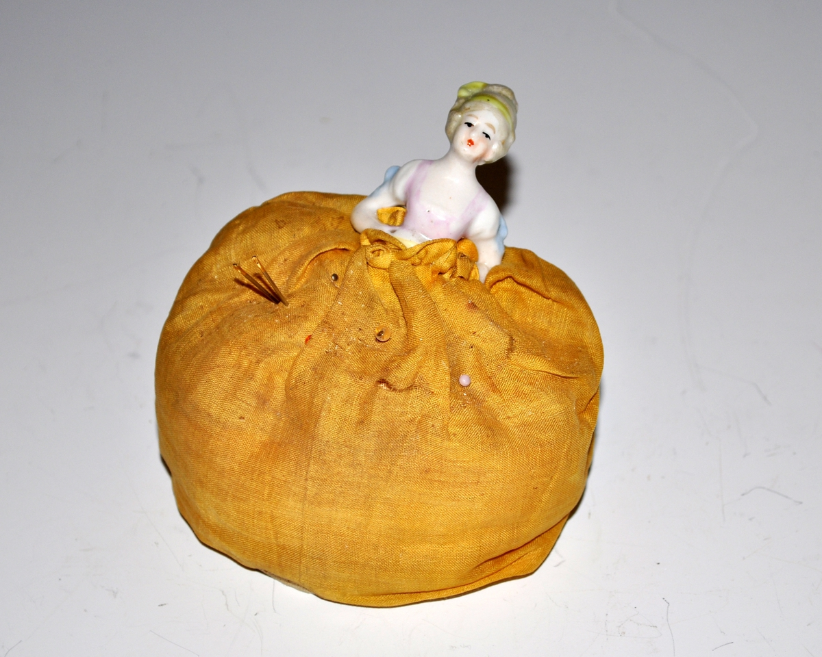 Fra protokollen: Nålepute i form av rokokko-dame. Hode og overkropp av porselen, selve puten, som illuderer kjole, trukket med gult stoff. Selve puten trukket med hvitt bomullslerret.