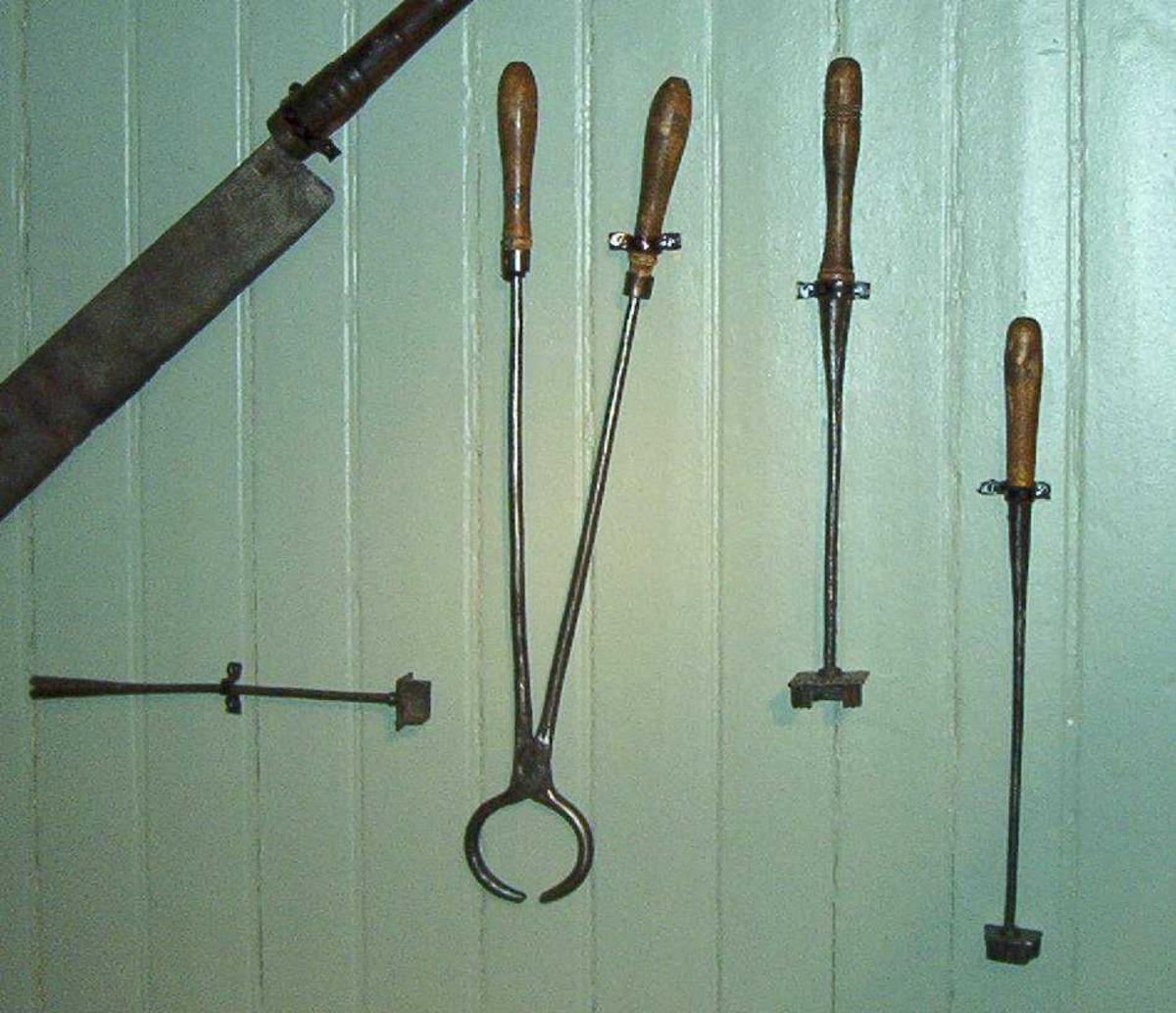 Tre jern for brennmerking. Motivet er en dobbel galge, et såkalt tyvsmerke. To av brennjernene har dreide trehåndtak, mens ett av dem mangler håndtak.