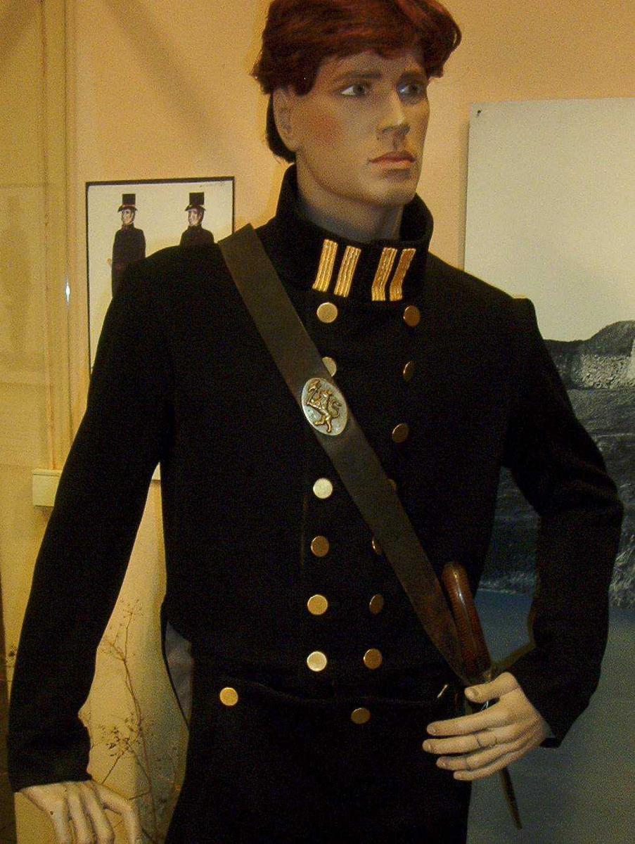 Mørkeblå dobbeltspent snippkjole i ull med distiksjoner i form av fire gule striper på kraven. 14 messingknapper i front. To messingknapper over snippen bak.