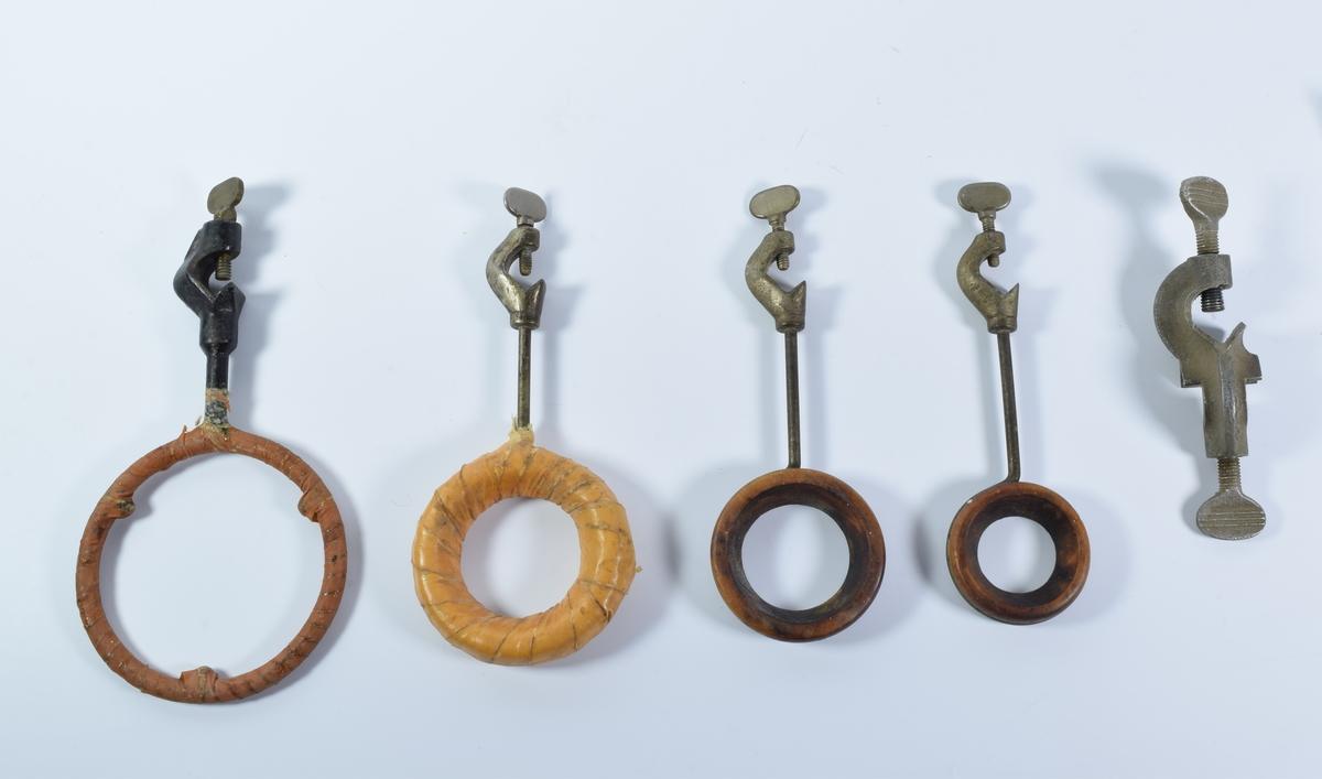 Fem stativarmer av metall til å feste på større stativ ved laboratoriearbeid. Fire av armene har ringer til å holde glasskolber, prøveskåler o.l. Den femte har to metallklemme som kan skrus til.  Stativarm a består av en svart jernstang og en jernring med tre utstikkende kuler på innsiden. Rundt ringen er det festet et brunt bånd eller teip.  Rundt ringen på stativarm b er det surret et tykt lag med stoff og deretter et lag med lysebrun teip eller lignende.  Stativarm c og d består av en jernstang og en jernring som er festet rundt en tykk trering.  Stativarm e består av to metallklemmer som strammes ved hjelp av en jernskrue.