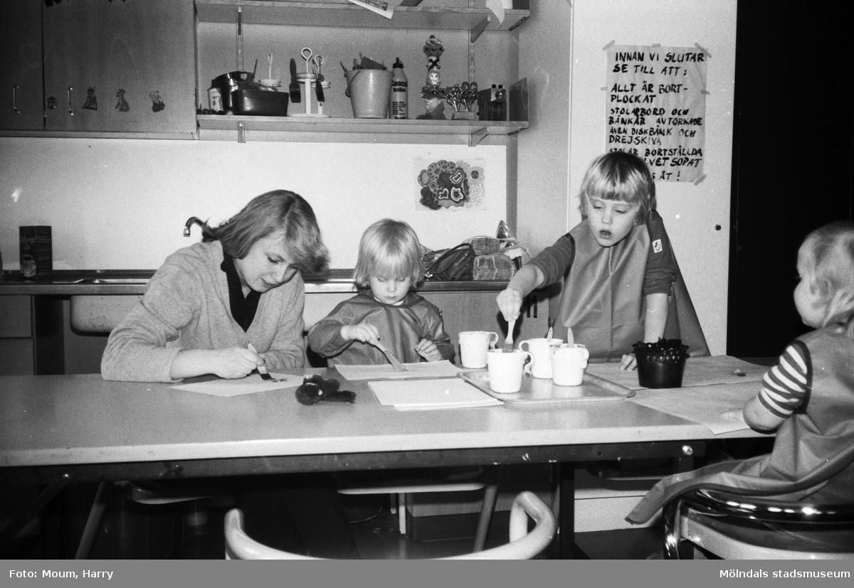 Öppen förskola på Almåsgården i Lindome, år 1983. Kvinna och barn sitter och målar.  För mer information om bilden se under tilläggsinformation.