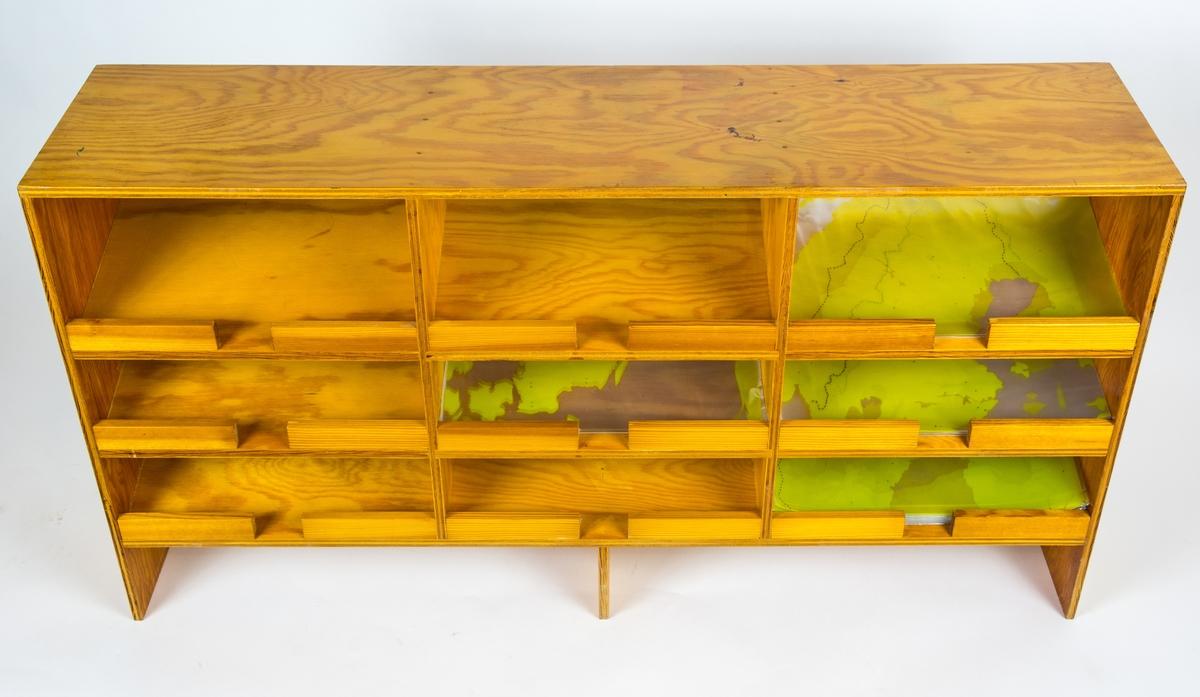 Förvaringshylla av trä till Samordningsbord bestående av tre hyllor med tre i varje fack i vardera. Hyllan skall sitta tillsammans med hylla FVM.151508 på kartbyrå FVM.151509.