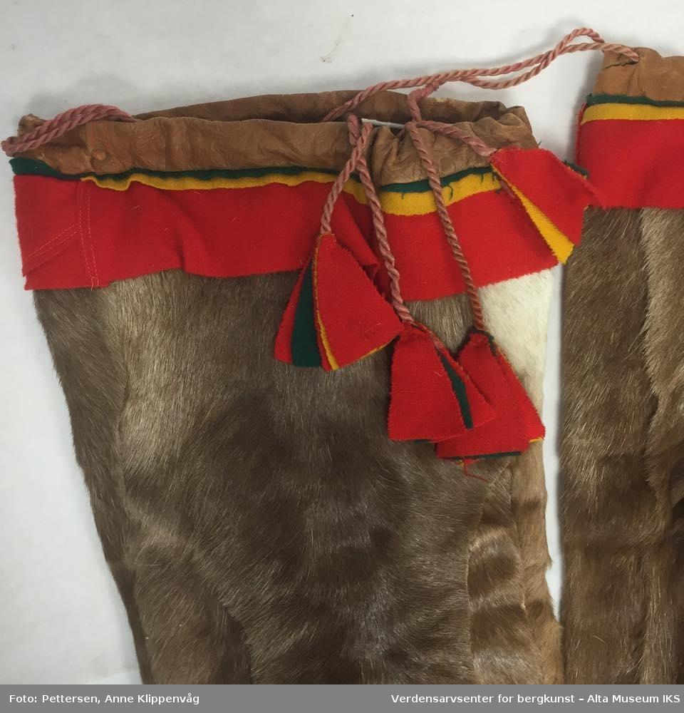 Ett par bellinger av reinpels. Nederst er det sydd fast med maskin rødt klede. På den øvre kanten er løpegangen og dekoren sydd på med for hånd med senetråd. Dekoren er av rødt, gult og grønt klede. Bellingen snøres med tvunnet skinn som er dekorert med fliker av rødt, grønt og gult klede.