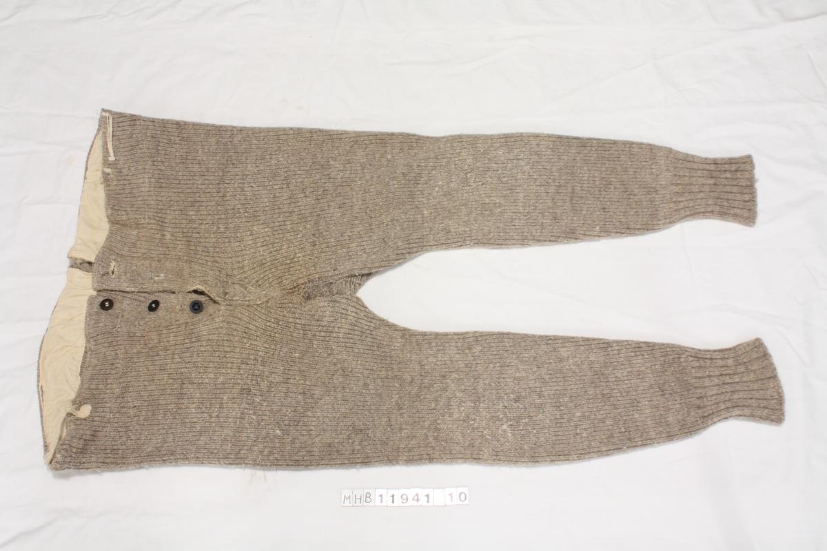 Strikkede ullunderbukser, lange. med hemper i bukselinning, trolig for å holde underbuksa på plass med seler eller festet til bukse eller genser over.