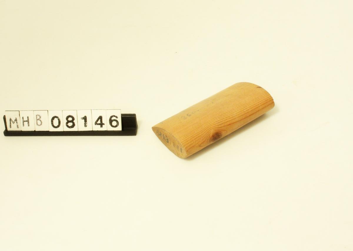 """Hovedform rektangulær med ovalt tverrsnitt. Den ene langsiden er tilspisset som egg. Skåret ut av ett trestykke. Langsidene har glatt overflaten, mens kortsidenes overflate er ru.  Merket bl. a.: """"felt 55 fr."""".  Til garnbinding."""