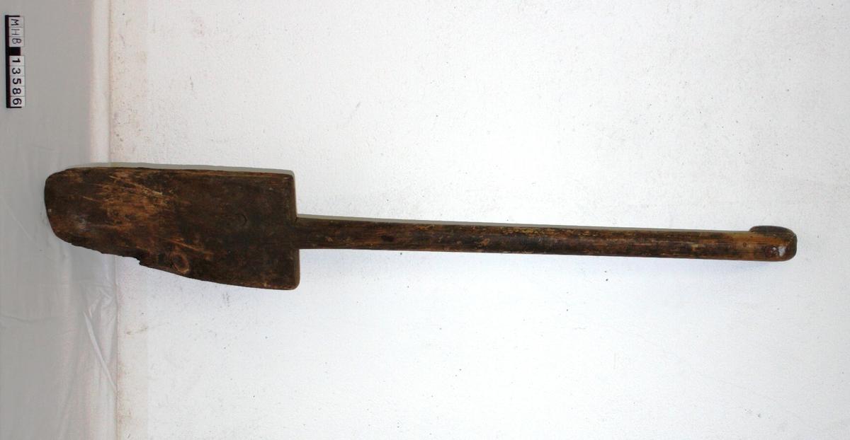 Spade med langt skaft av tre som øverst bøyer seg bakover til et håndtak. Håndtaket er laget ved at en liten tredel er spikret fast til skaftet. Nederst går det ut i et treblad som er rettvinklet i de øverste hjørnene, og buet nede. Noe treverk mangler nederst på spaden