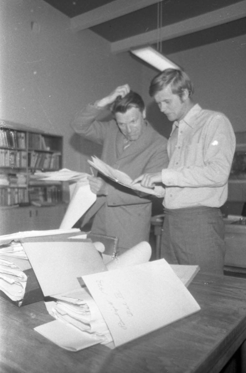To menn som studerer diverse sakspapirer.