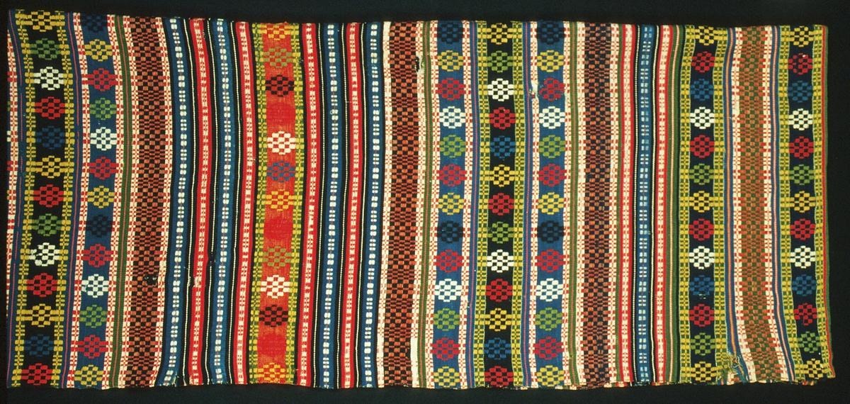 """Randigt täcke vävt i munkabälte på botten i inslagsrips. Olika breda bårder med mönster i plockat och skyttlat munkabälte, däremellan ränder i inslagsrips. Färger: två nyanser blått, två nyanser rött, tre nyanser grönt samt gult, naturvitt, blåsvart och brunsvart. Täcket är ihopsytt på mitten, med oblekt lingarn och en bit med svart björntråd, av två ca 610 mm breda vävlängder. Stadkanter i långsidorna, handfållat i kortsidorna. Varp i oblekt 2-trådigt s-tvinnat lingarn, 6 trådar/cm. Inslag i 1-trådigt z-spunnet ullgarn, ca 29 inslag/cm, enkelt i botten, två trådar tillsammans i mönster. Märkt på baksidan med påsydd tyglapp med texten: """"Skytts h.d. N° 241"""".(Del av halva täcket på bild)."""
