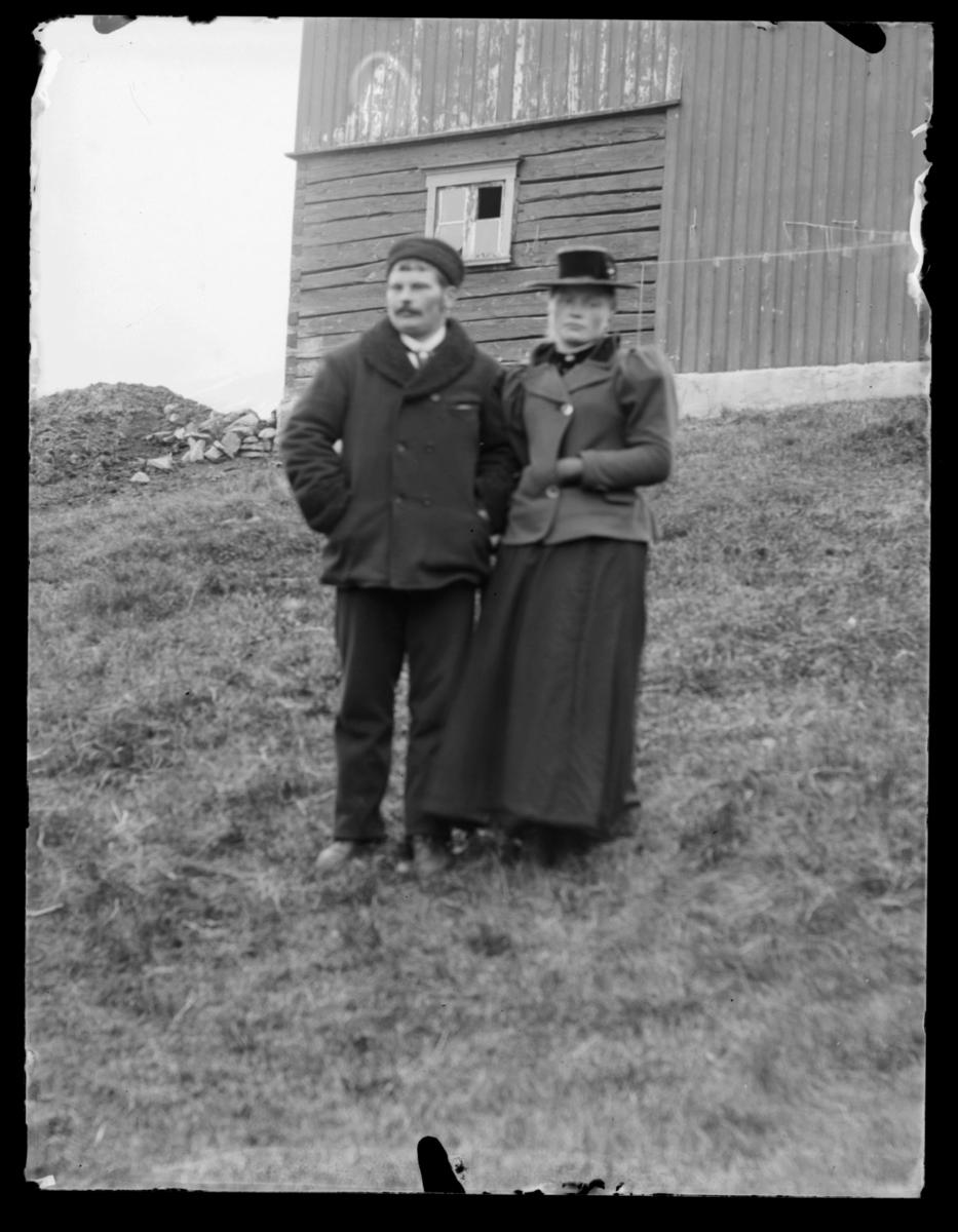 Ukjent par fotografert foran en bygning