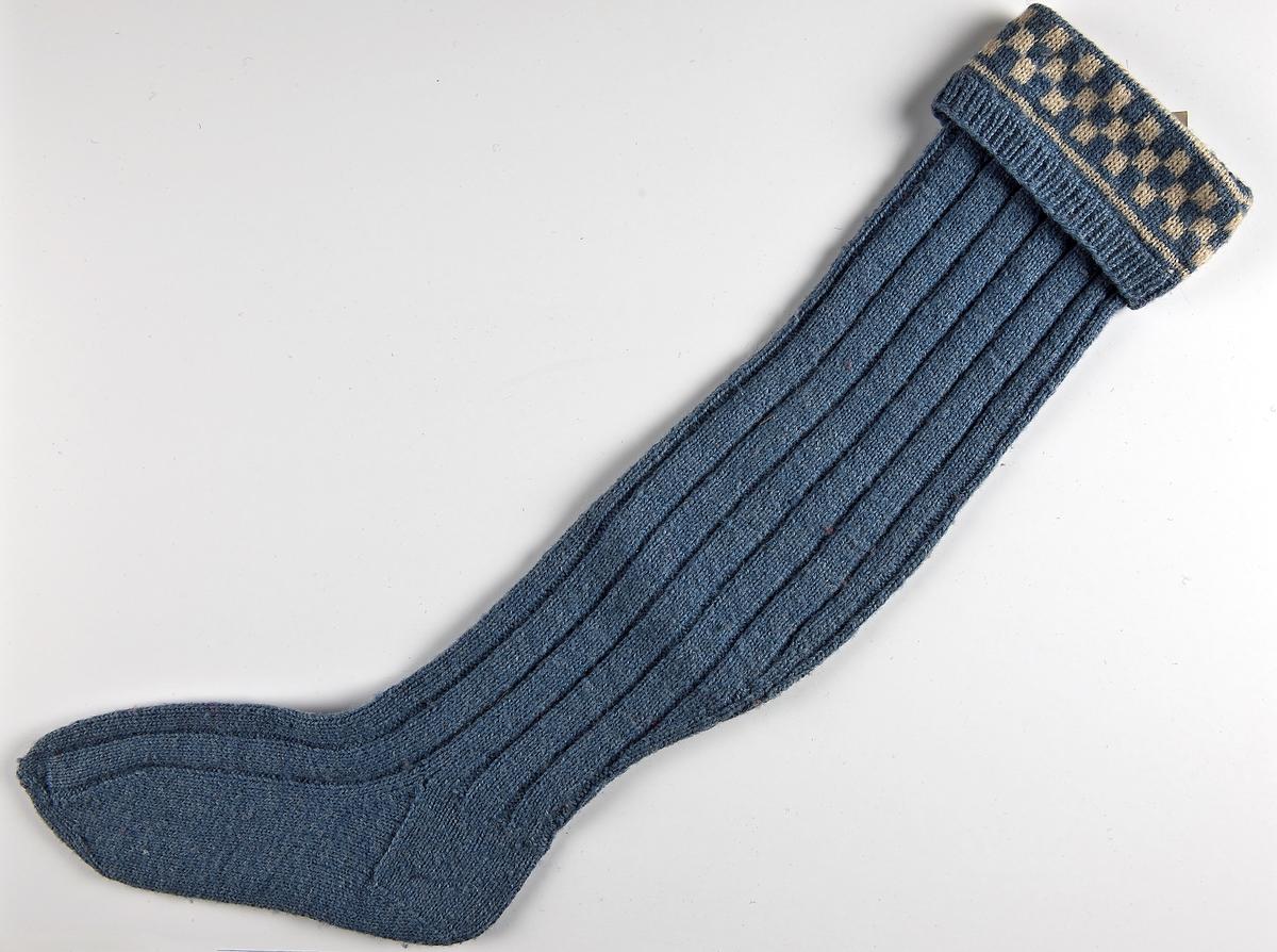 Strumpa i ljusblått 3-trådigt och naturvit 2-trådigt ullgarn.skaftet har resår (1 rät 1 avig) i 2 cm sen en rätstickad rutbård och därefter en bredrandig (5 rätt-2 avig) resår ut över tån,häl och under fot slätstickad.