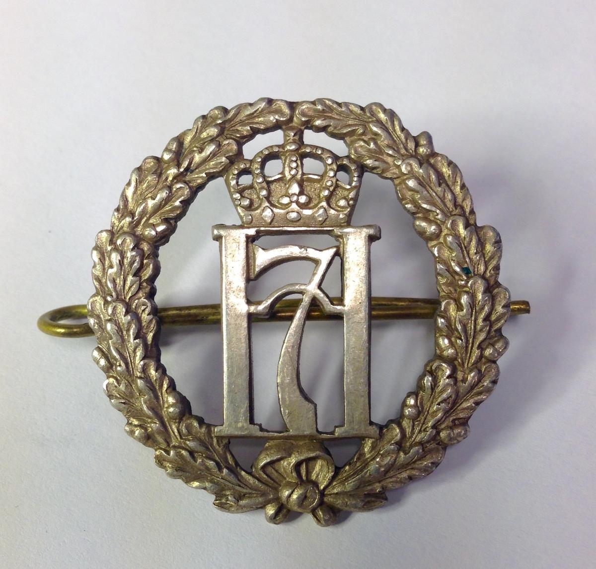 Luemerke i sølvfarget metall. Eikeløvskrans med kong Håkon VIIs merke (H7)