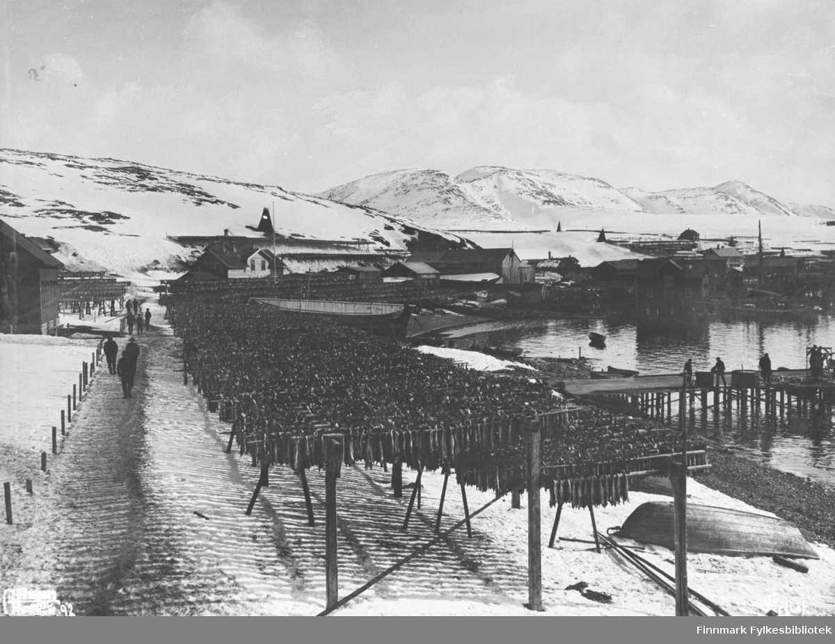 Fiskehjeller ved fjæra i Hammerfest. Ved hjellene går en sti/ smal grusveg der det går folk / menn. Noen menn jobber på kaia lengre inn på bildet. En del av byen ses i bakgrunnen der det står noen hus, pakkhus og andre byggninger.