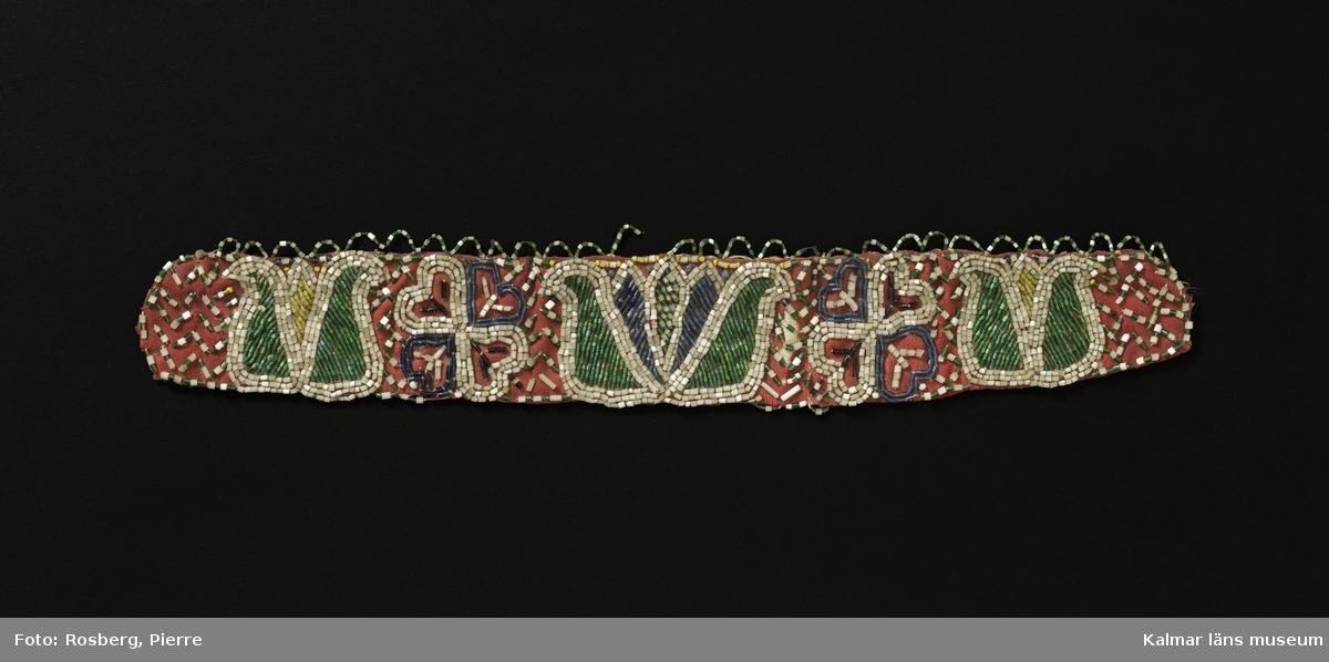KLM 4603:1. La. Brud-la. Pärlkrans. Pärlbesatt band. Av rött kypertvävt ylletyg. Rikligt broderad med gröna, vita, blå och svarta glaspärlor, rörpärlor. I mitten tulpan omgiven av stjärna eller blomma och tulpan. Längs överkanten kantad med udd av vita och gröna pärlor trädda på metalltråd, rester finns av lika udd längs nederkanten. Det röda ylletyget är sytt mot ett grövre oblekt tuskaftat linne. Broderiet är sytt genom båda tyglagren. Utan nacklapp.
