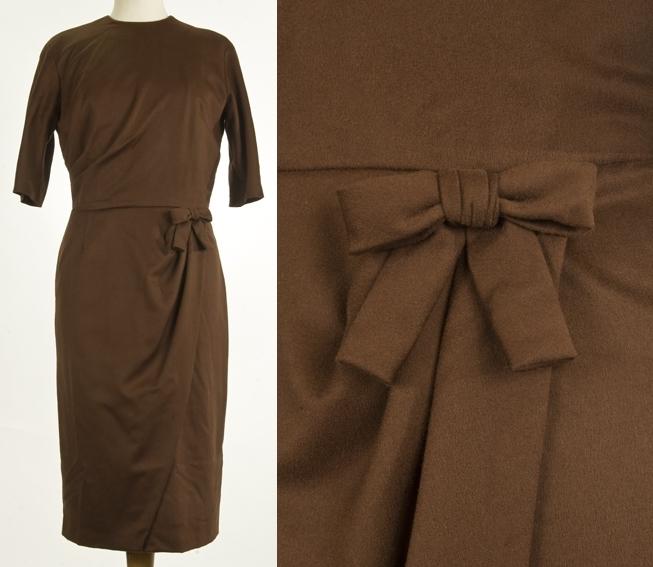 Kjole uten krage, 3/4 lang erm. Sløyfe på venstre side i livet. Skjørt med skrå fold foran.