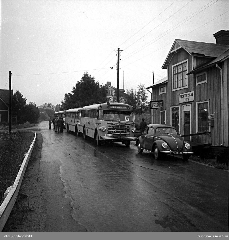 Pensionärsutflykt med avgång från Skönviksvägen där fyra bussar står färdiga för påstigning. Till höger syns dåvarande Skönviks varucentral (numera riven) och längst bort skymtar Gångvikens skola.