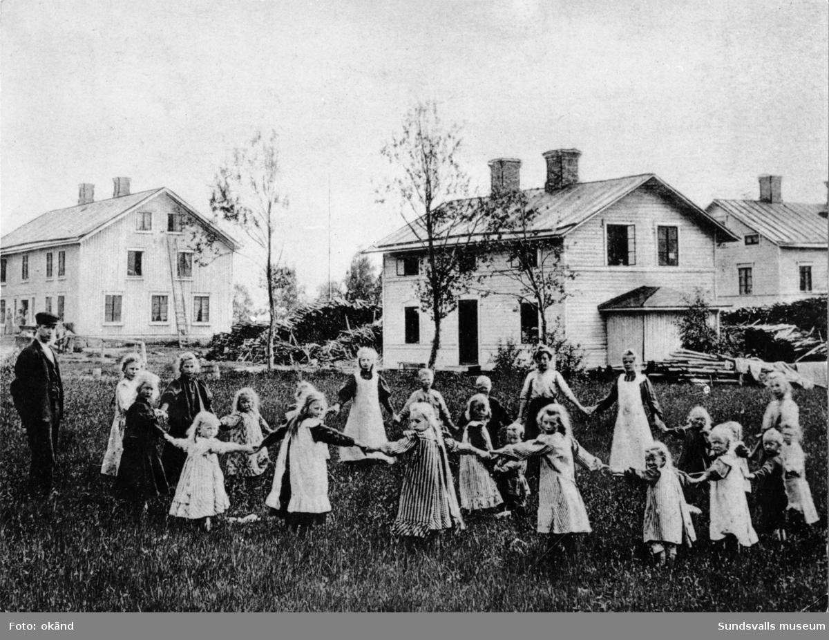 Fjäls glasbruk. Midsommarfirande. Dans kring majstången. I dansen deltog både patronens och glasbruksarbetarnas barn. Huset närmast barnen är den enda byggnad med koppling till glasbruket som finns kvar idag (2015).