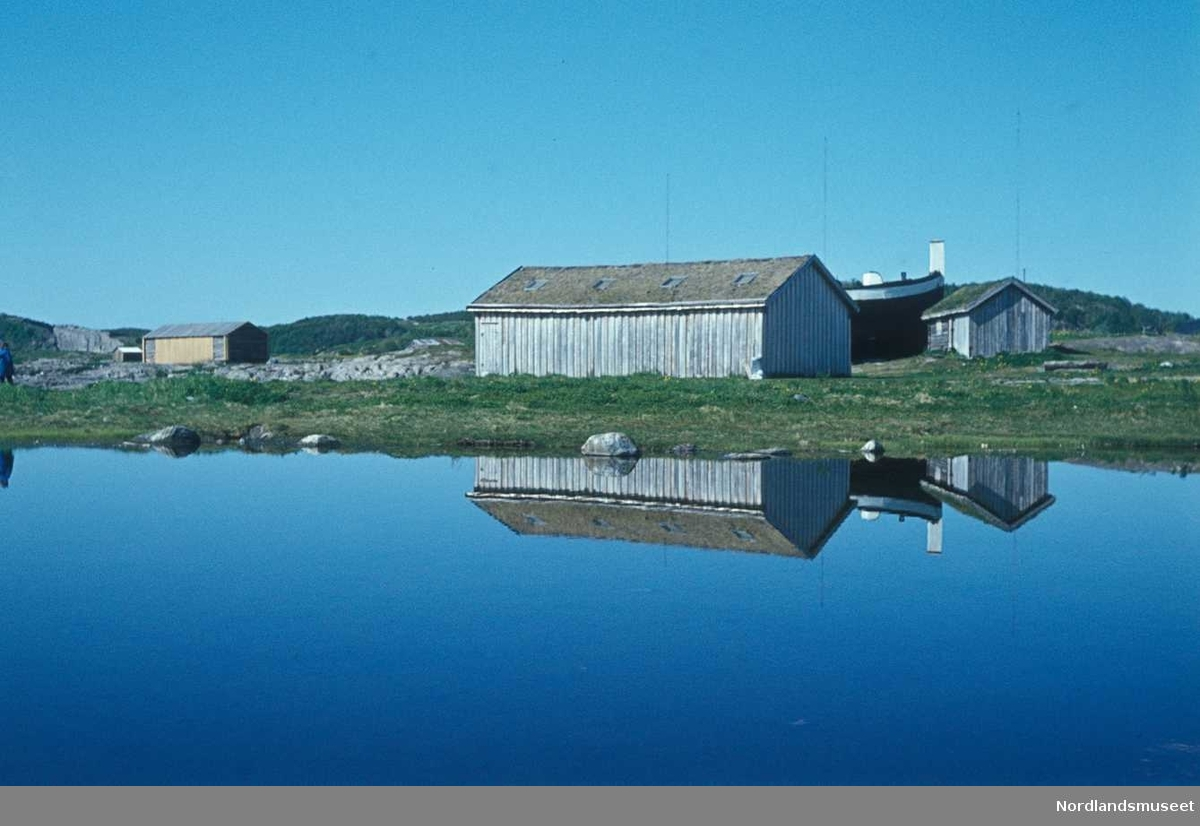 Dias fra Bodøsjøen frilufts museum, vi ser et umalt båthus med stående panel og torvtak, og ved siden av en mindre bu, bak sees jekta Anna Karolina delvis skjult av båthuset, forran ligg er havet speilblankt og det er gjenskinn fra husene, i kanten sees også en annen bygning, bak er det blå, klar, himmel.