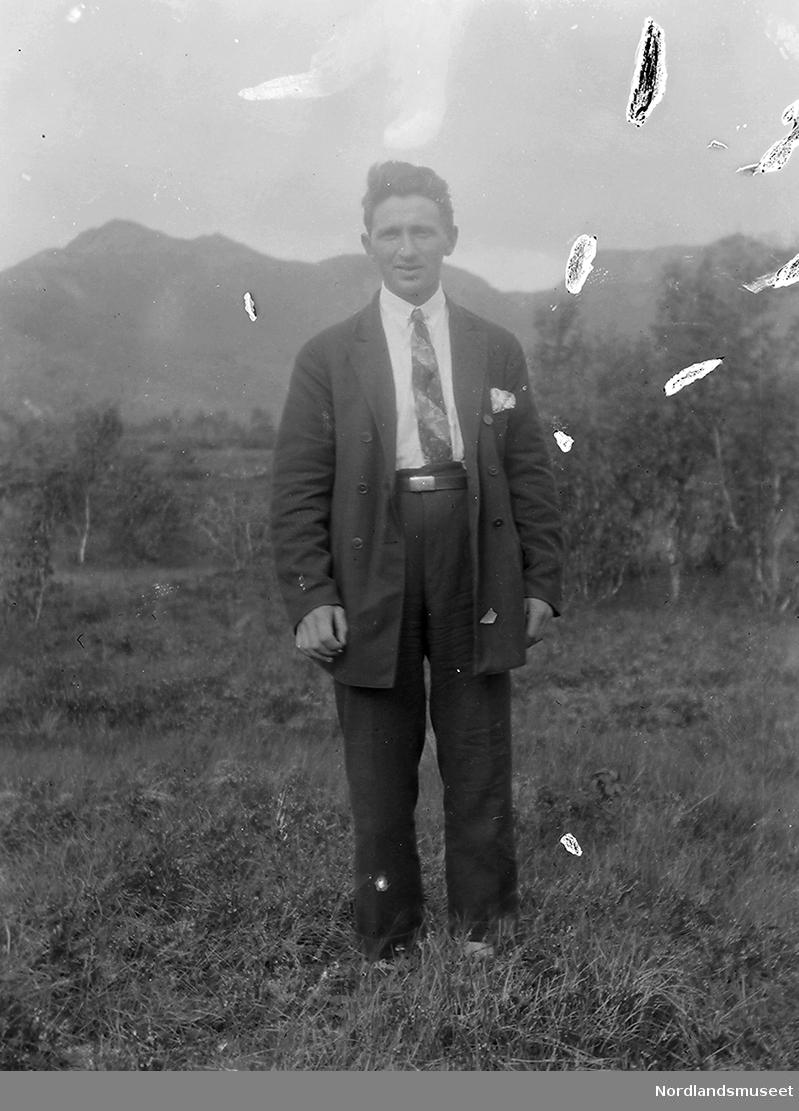 Mann stående i en eng med lyng og bjørkeskog i bakgrunn.