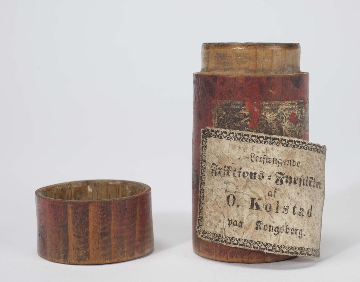 Rødmalt dreid fyrstikkhus i tre med lokk. Delvis løs etikett med innskrift. Eldre etikett under denne.