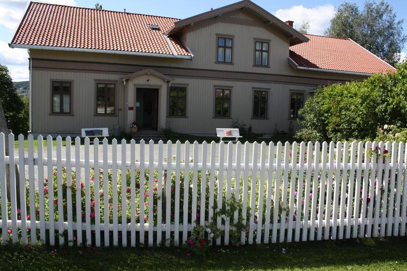 Inngangspartiet Kvinnemuseet med stakittgjerdet og rosebed. Sommerdag med solskinn. Foto/Photo