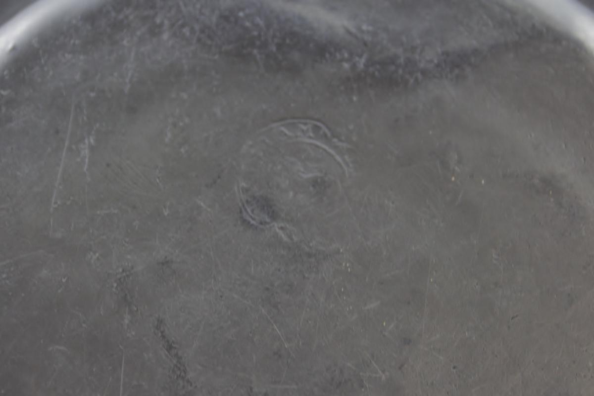 Liten tinntallerken, flat og sirkelrund. Bunnen prydet med en sirkellinje. kanten horisontal med gravert linje ved randen. Delvis uleselig stempel på baksiden.