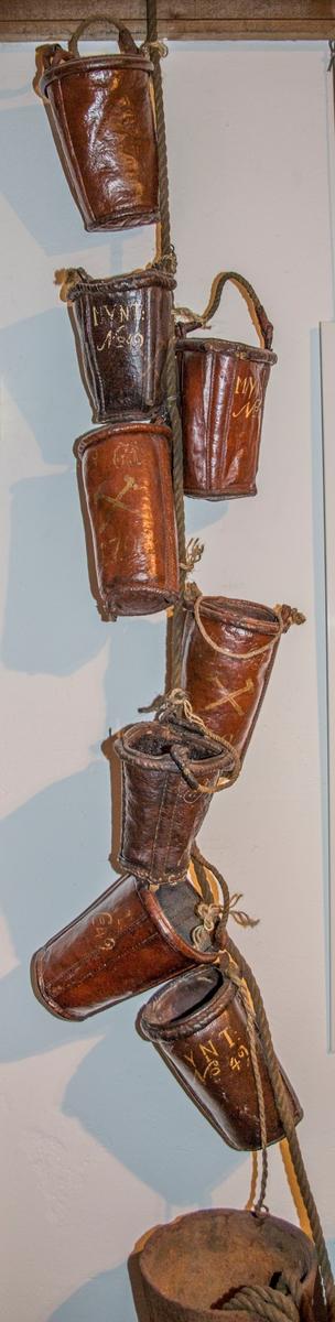 Brannbøttene er laget av to lærdeler som er sammenføyet med søm. Det er sydd inn to tre-spiler, som går fra kanten av bøtteåpningen og og ned til bunnen. Disse er plassert vis-a-vis hverandre i forhold til bøttens diameter. Trespilene fungerer antagelig som forsterkning både av bøtten og hankefestet. Bøttene er malt med rødbrun farge både utenpå, inni, og i bunnen. Overflateundersøkelse med mikroskop viser et tynt malingslag. Malingen har trengt inn i porene i læret. Bøttene er påført nummer, eierbetegnelse og årstall med gulhvit maling. Alle malingslag fester godt til underlaget. Læret er stivt og hardt. Bøttene har vært innsatt med bekk innvendig for at de skulle være vanntette og det finnes enda rester av bekk på noen av dem.