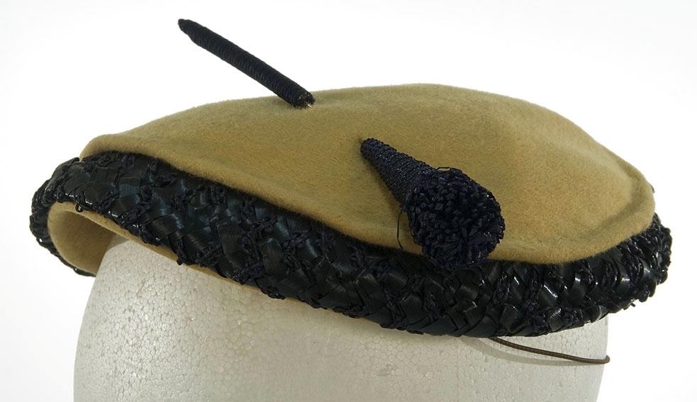 Flat liten hatt med kant av blå tråd og og bast.