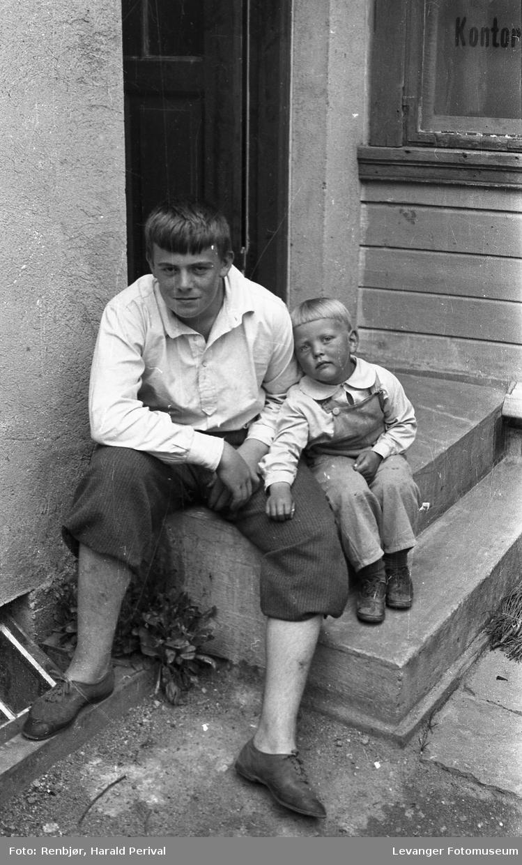 Per Renbjør og en liten gutt på trappa ved foto og musikkforretningen.