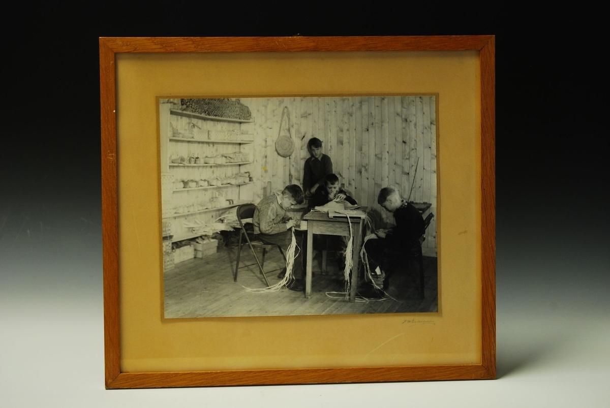 Fotografi av fire gutter som arbeider med flettearbeid.