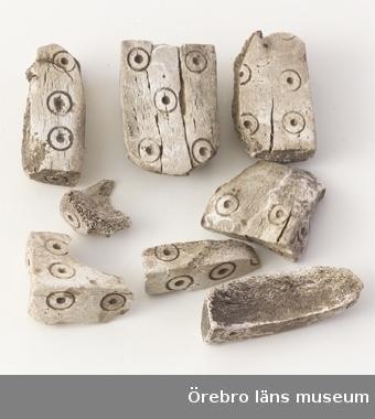 Tärningar från järnåldern. Av ben, åtta fragment, ornerade med koncentriska cirklar. Rektangulära. Från Närke, Hardemo socken, Skeftasberget grav 1, Sigtryggskullen. Fynd tillsammans med: pärla, beslag och armringsfragment av brons, bälteshake, bältesbeslag, beslag, brodd, spikar, nitar, bleck samt fragment av järn, pärla och spelbricka av bergskristall, glas- och flusspärlor, kamfragment och spelbrickor av ben, krukskärvor, blästermunstycke av lera, flin-, skiffer- och kvartsit, järnslagg, obestämd slagg, brända ben samt kol.  Utställt på Länsmuseet i basutställningen år 2001.  Sex stycken fragment i magasin 1996, två stycken utställt på slottet 1996.