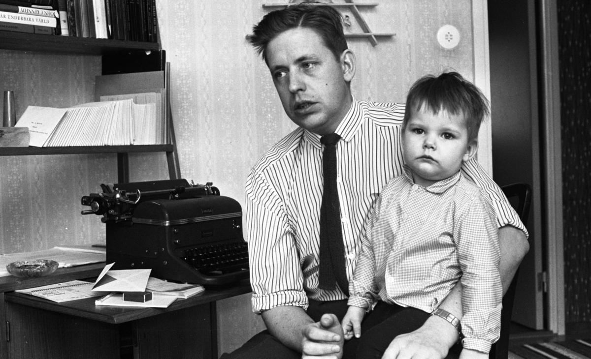 """Kontakt-kille som skriver brev, 4 mars 1966I förgrunden syns det en man som är klädd i en ljus, randig skjorta med en mörk virkad slips och mörka byxor. Han har en kortklippt frisyr. På mannens vänstra ben sitter det en pojke som är klädd i en långärmad skjorta och mörka byxor. Till vänster på bilden ser man en bokhylla. Bland böckernas rubriker i bokhyllan syns det endast """"John Kennedy"""" och """"I vår underbara värld"""" av J. V. Stanêk tydligt. På bordet under bokyllan står det en skrivmaskin, en ask med tändare, ett askfat, ett anteckningsblock, pappershäften och ett kuvert. Skrivmaskinen är märkt """"Halda."""" I bakgrunden till höger ser man en dörröppning."""
