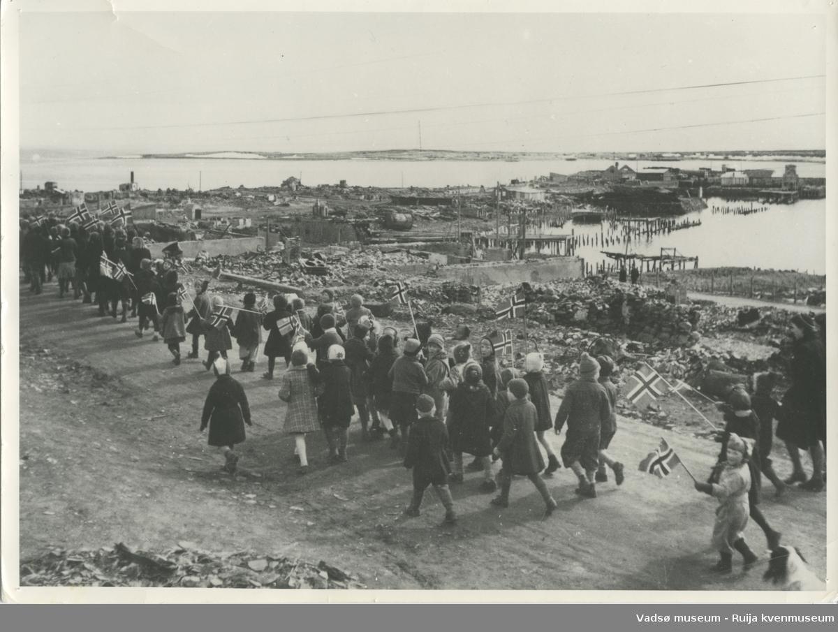 17-mai tog gjennom Vadsøs gater, rett etter krigens slutt. I bakgrunnen ses det ødelagte sentrumsområdet.