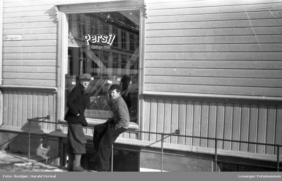 To gutter foran en butikk med reklame for Persil på vinduet.