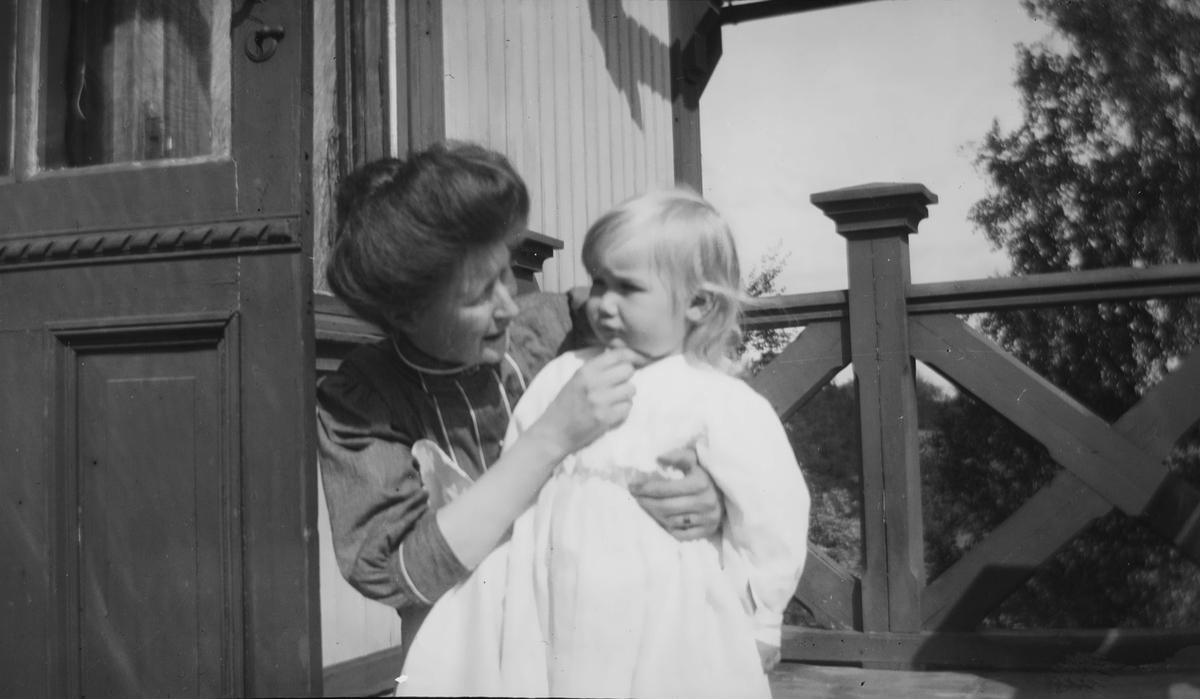 En kvinne sitter på huk og holder rundt en liten sommekledd Iacob Ihlen Mathiesen.