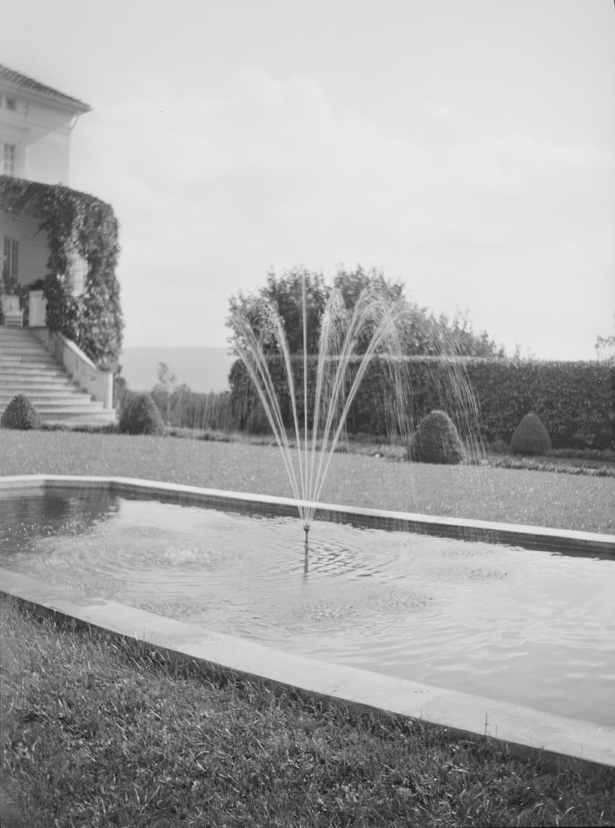 Hagen på Linderud Gård ved sommerstid. I front sees en avlang åttekantet dam med murkanter. I midten er det en fontene. I bakgrunnen sees friserte busker og hekker samt hovedhuset med en veranda som er dekket av klatreplanter.