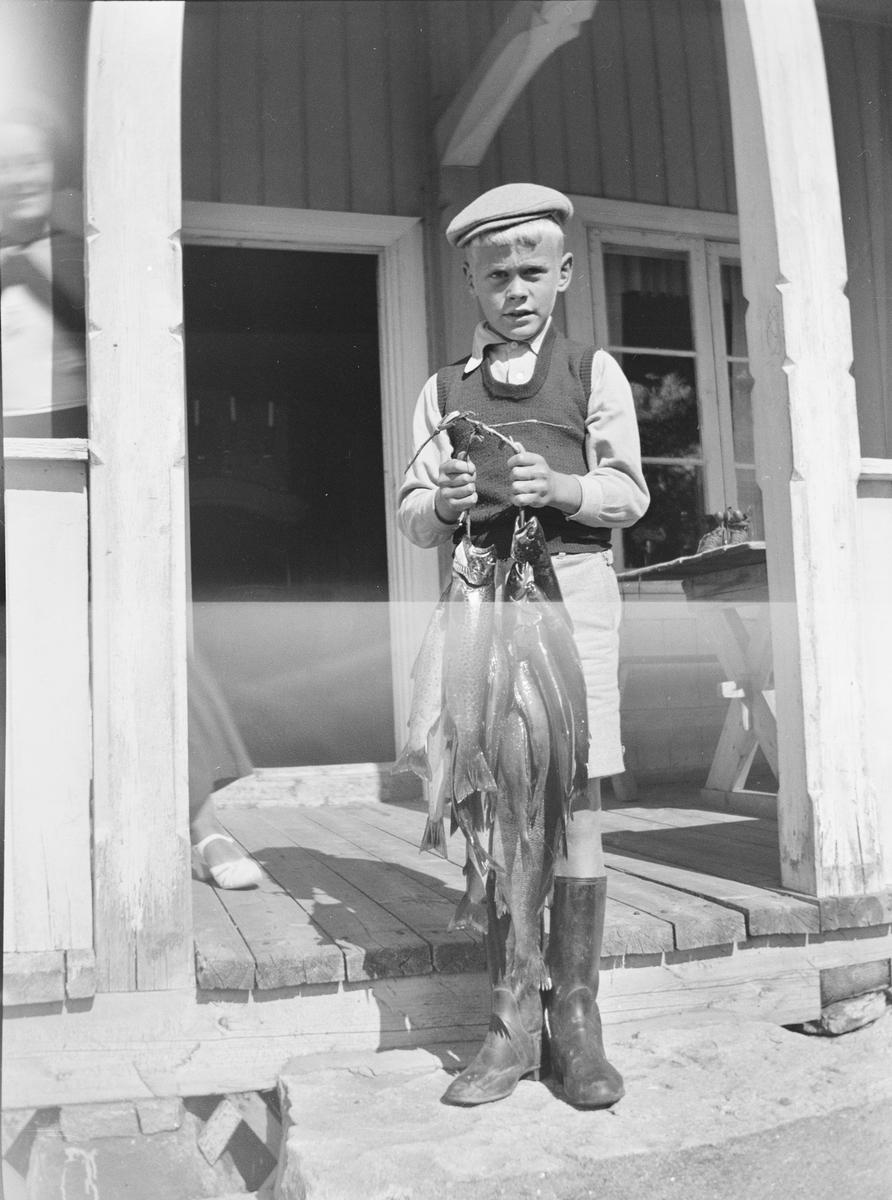 En gutt, Ole, står på verandatrappen og holder opp en fangst med fisk. Fisken er tredd på en snor. En kvinne, Jil, skjuler seg bak en søyle.