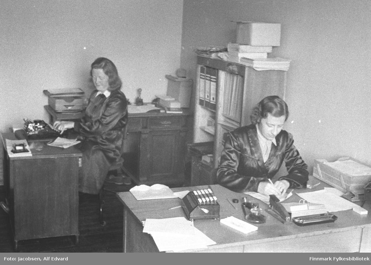 To damer sitter ved hvert sitt skrivebord. De er Randi Simonsen til venstre og Karen Iversen til høyre. Bildet er sannsynligvis fra et av Televerkets kontor i Hammerfest. Begge damene har ganske mørke frakker med lyse bluser under. På det nærmeste, ganske lyse skrivebordet, står en lys arkivkurv helt til høyre. Eller kan hullemaskin, blyantbrett, stiftemaskin, bordkalender og litt papir ses. En boks med knapper/taster som kan være en telex står til venstre på skrivebordet. Skrivebordet til venstre på bildet er ganske mørkt og oppå står en manuell skrivemaskin som damen skriver på. Litt papir ligger også på det skrivebordet. Rett bak damene står en bokhylle med flere ringpermer og hefter. Noe papir og en eske ligget oppå. Et skrivebord som står bak damen til venstre på bildet er ganske mørkt. Det har små skuffer under bordplaten og et skap på høyre side. En arkivboks står rett ved siden av damen. Lenger bort ligger noe papir og et stempel og eske ses også. Kontoret har forholdsvis lyse veggger.