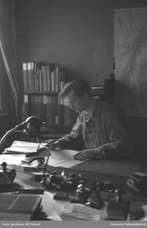 Fridtjof Jacobsen arbeider på sitt kontor i Televerket. Han sitter ved et skrivebord iført en lys skjorte. På skivebordet foran han ligger endel papirer. En leselampe på skrivebordet ses helt til venstre på bildet. Nærmest kamera ses endel kontorutstyr som hullemaskin, bordkalender, binderskopp, stempel og penn i blekkhus. På den ensfargede, lyse veggen bak han henger et stort kart over Nord-Norge. Til venstre for det står en bokhylle som er full av ringpermer, bøker og hefter. En arkivboks står helt til høyre på hylla.Til venstre på bildet ses ene siden av forholdsvis lyse gardiner.