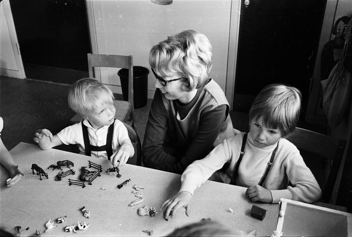 Förskolepersonal och barn leker med leksaksdjur, Akademiska sjukhus.