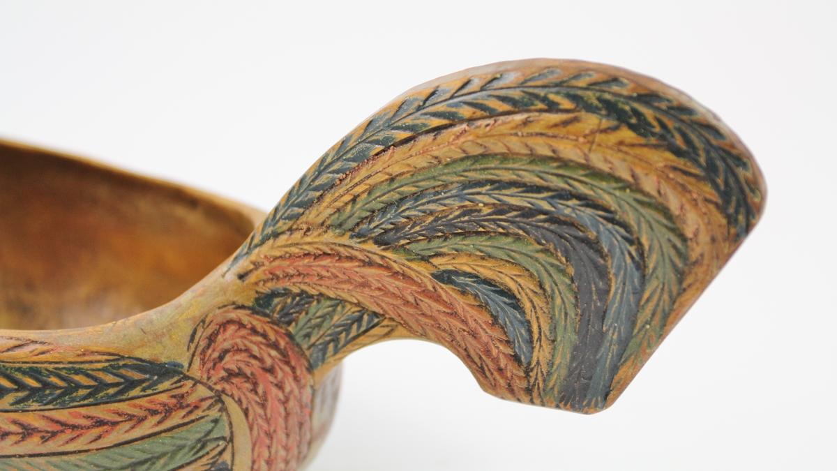 Ølhøne i tre. Oval grunnflate, korpus rundet, innsnevret mot randen. Naturalistisk hals, hode og vertikal hale, innrissede fjær malt i rødt, grønt og blått.