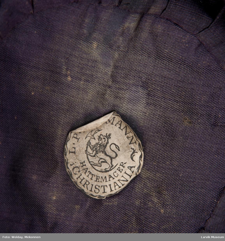 """Form: """"á l'androsmane"""", sort filt med blank lo, på  forsiden kokorde med gullmetallsnor, festet til gullmetallknapp med riksløve, et knippe metallsnorer i hver side,svettebånd av sort skinn, ilagt avis fra 1906, sidene var nestet sammen med pullen."""