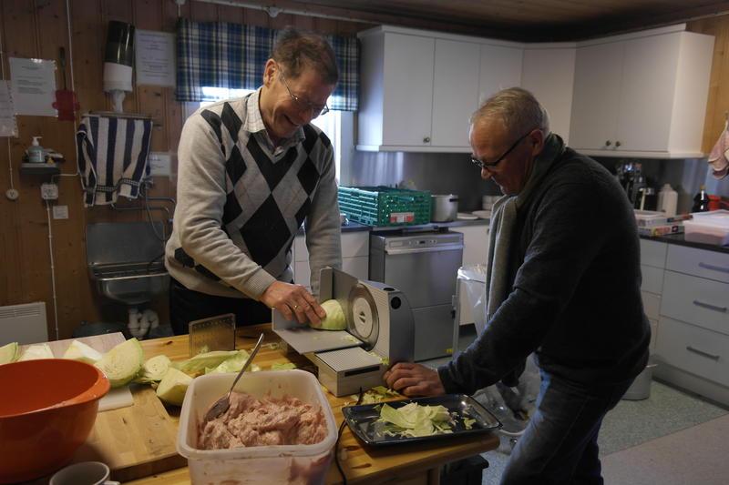 "to menn skjærer kål til surkålen som skal serveres på  ""Førjul på bygdetunet""."