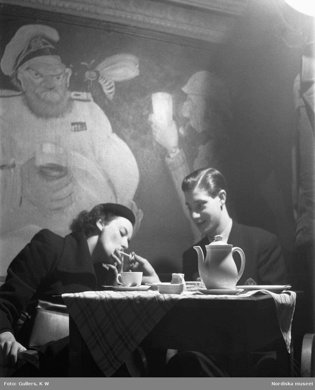 Ungdomar på konditori. En ung kvinna får cigaretten tänd av sitt manliga sällskap.