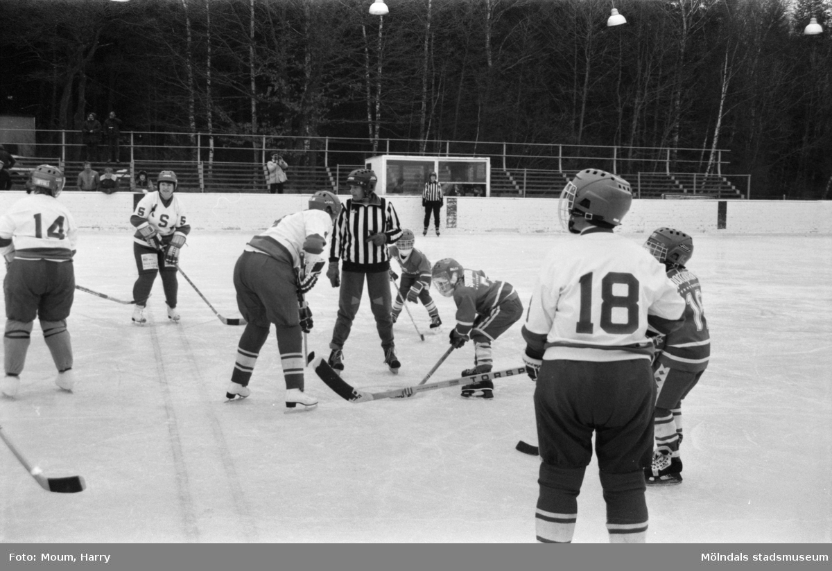 """Kållereds SK ishockeylag 75:or möter ett """"mammalag"""" på Kållereds isbana, år 1984. """"Domare Ingela Samuelsson vid tekningen. Domare II längst bort Monika Karlsson.""""  För mer information om bilden se under tilläggsinformation."""