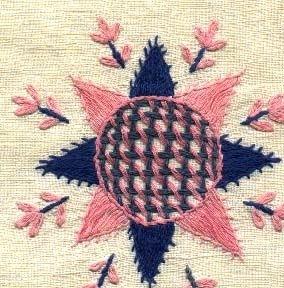 Fyrkantig broderad duk i Hallandssöm. Broderad på blekt linne med rosa och två blå nyanser bomullsgarn. med mönsterformer som stjärnor, blommor och en sick-sack bård runtom. Duken är handfållad