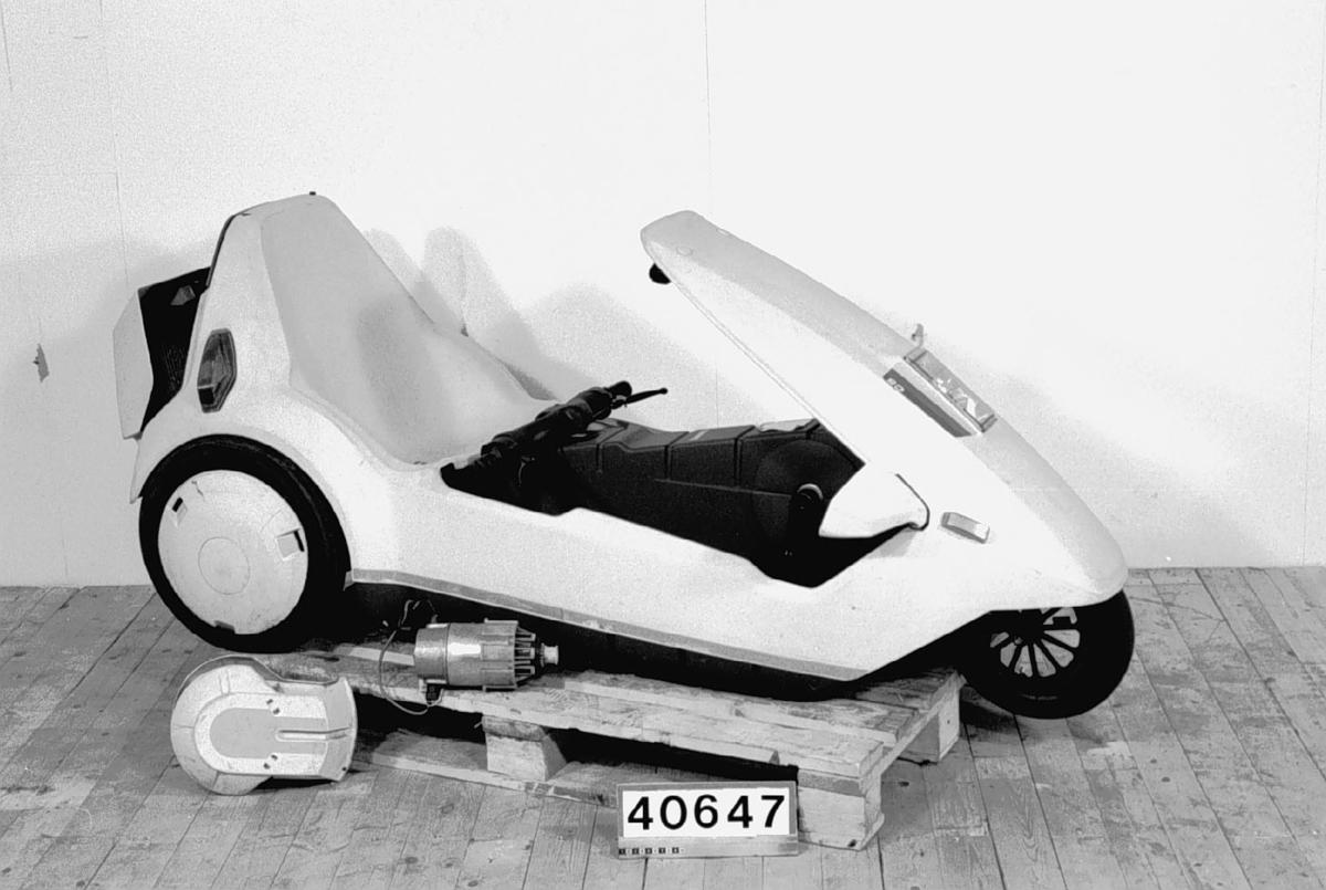 En trehjulig elektrisk moped konstruerad av Clive Sinclair. Hoover tvättmaskinsmotor driver bakhjulen. Batteri av typ mc- startbatteri. Kaross av gråvit plast.  Motor 12 volt, 259 Watt, 3300 varv per minut Körsträcka 2-3 mil.