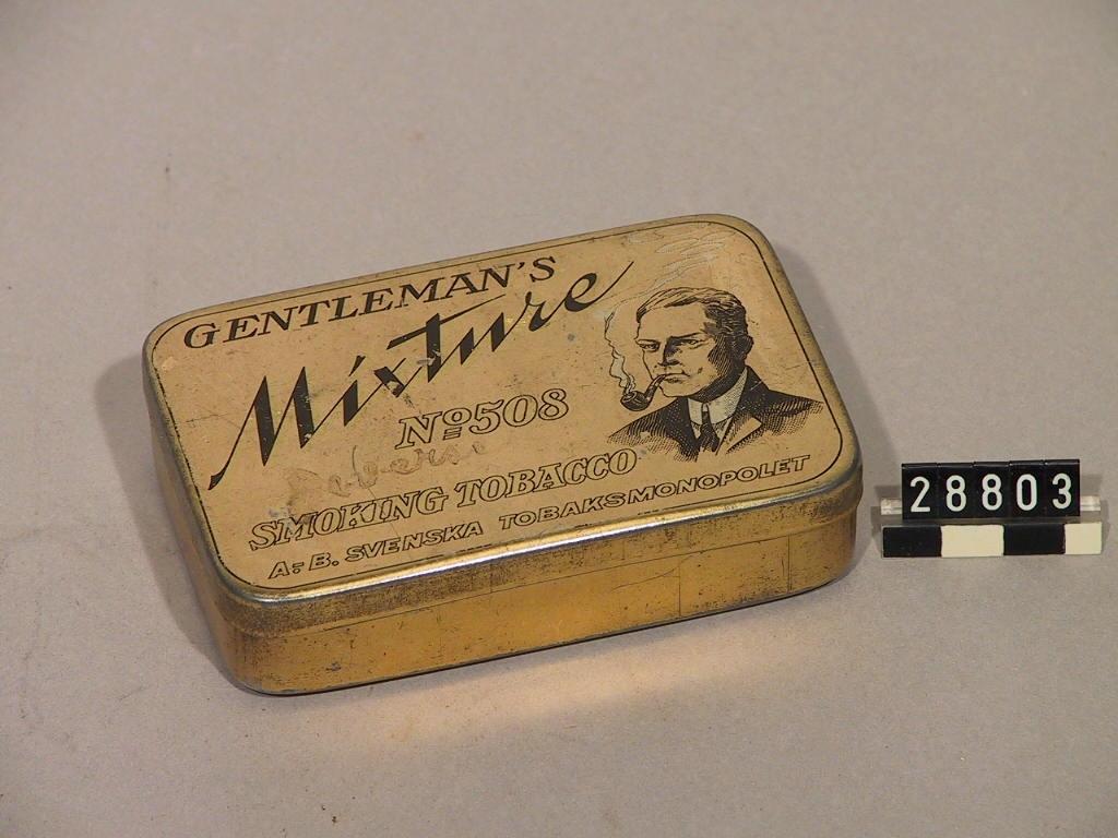 """Smoking Tabacco i bleckburk med gångjärnslock med färglitografi. """"Gentleman's Mixture No508""""."""
