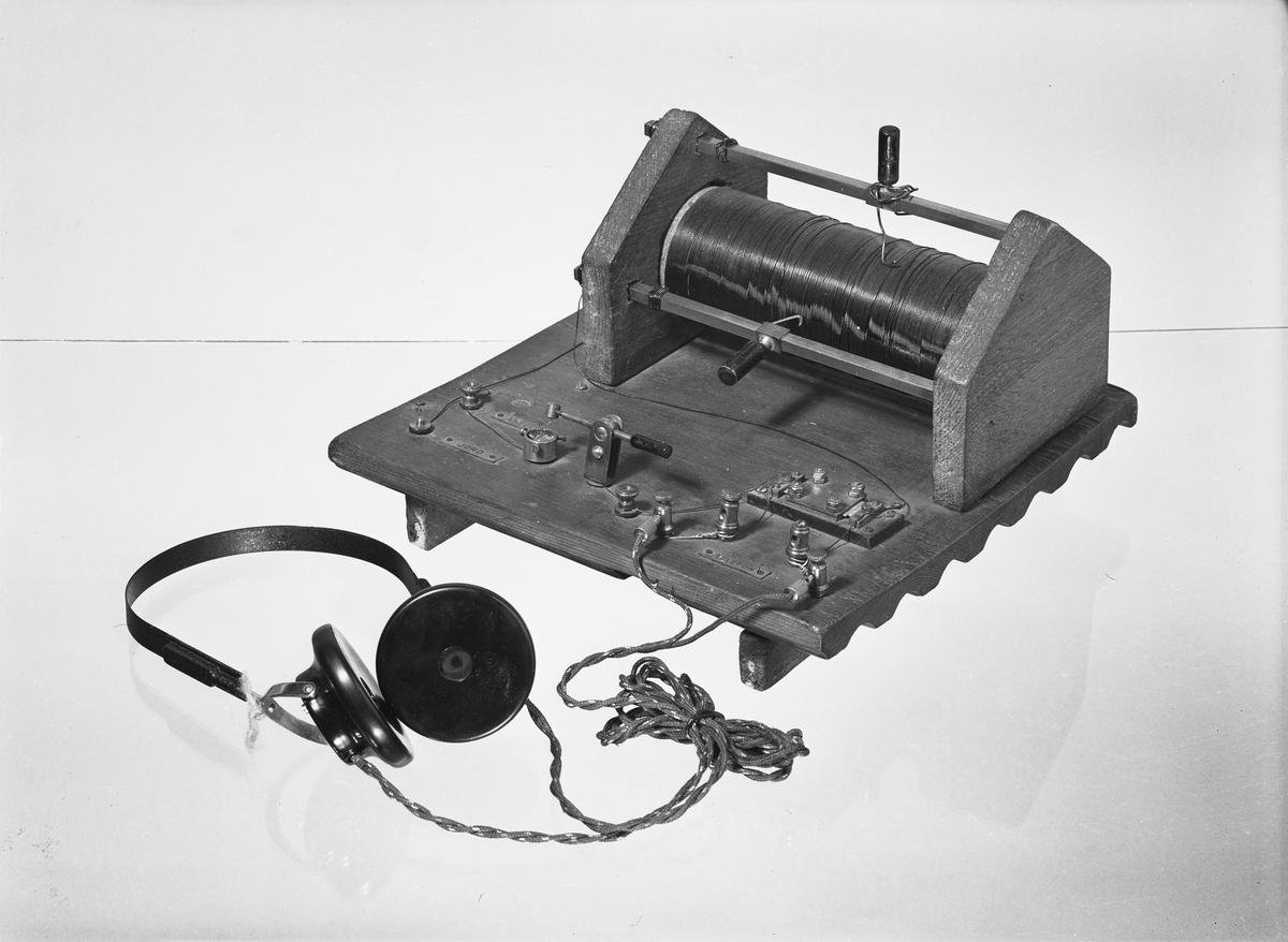 Amatörradiomottagare, monterad på stycke av ritbräde. Kristallhållare, skyltar och kondensator är handelsartiklar från år 1923, ditsatta senare. Dubbel hörlur i bygel. Kristall saknades vid ankomsten.