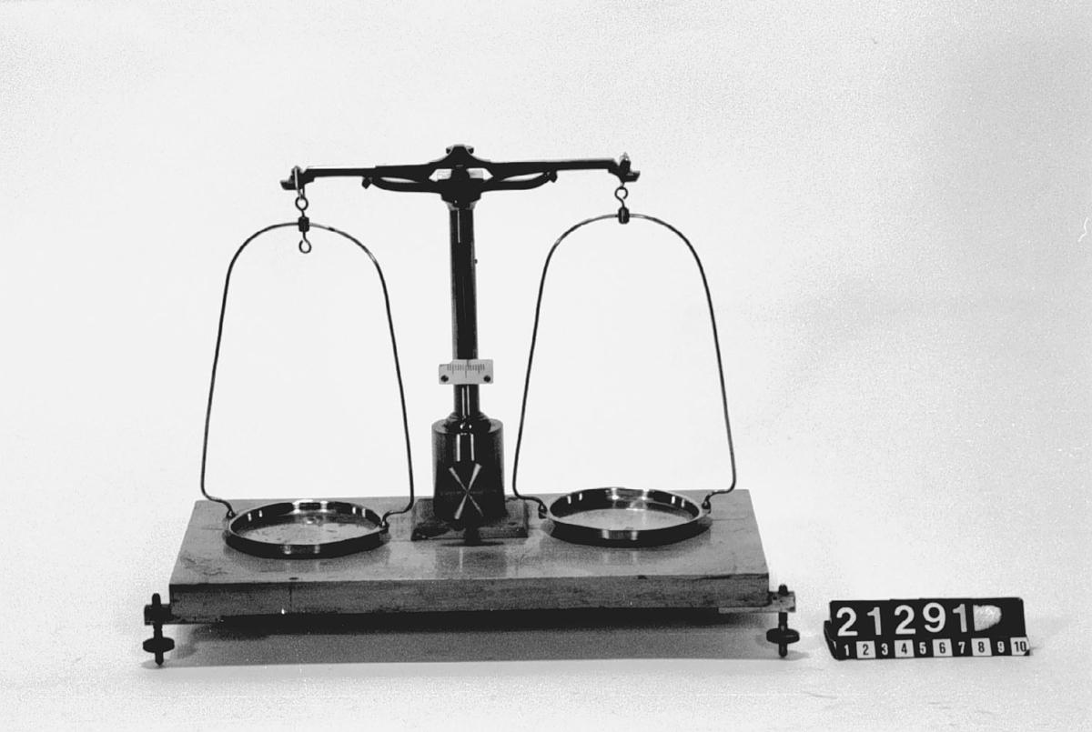 """Finare balansvåg med arretering jämte viktsats 0.01-100 gr. Skylt: """"L. Reimann Berlin"""". Balansen märkt: """"8"""". Etui för vikter, längd:130 mm, bredd: 90 m, höjd: 40 mm, vikt: 0.5 kg. Tillbehör: Patta med ståndare, balans, två skålar med byglar, viktfodral av trä med vikter av mässing: 100, 50, 20, 2 st 10, 5, två 2, 1 g och troligen av nickel 0.5, två 0.2, 0.1, 0.05, 0.02 och 0.01 gr samt glaslock (pincett och en vikt saknas)."""
