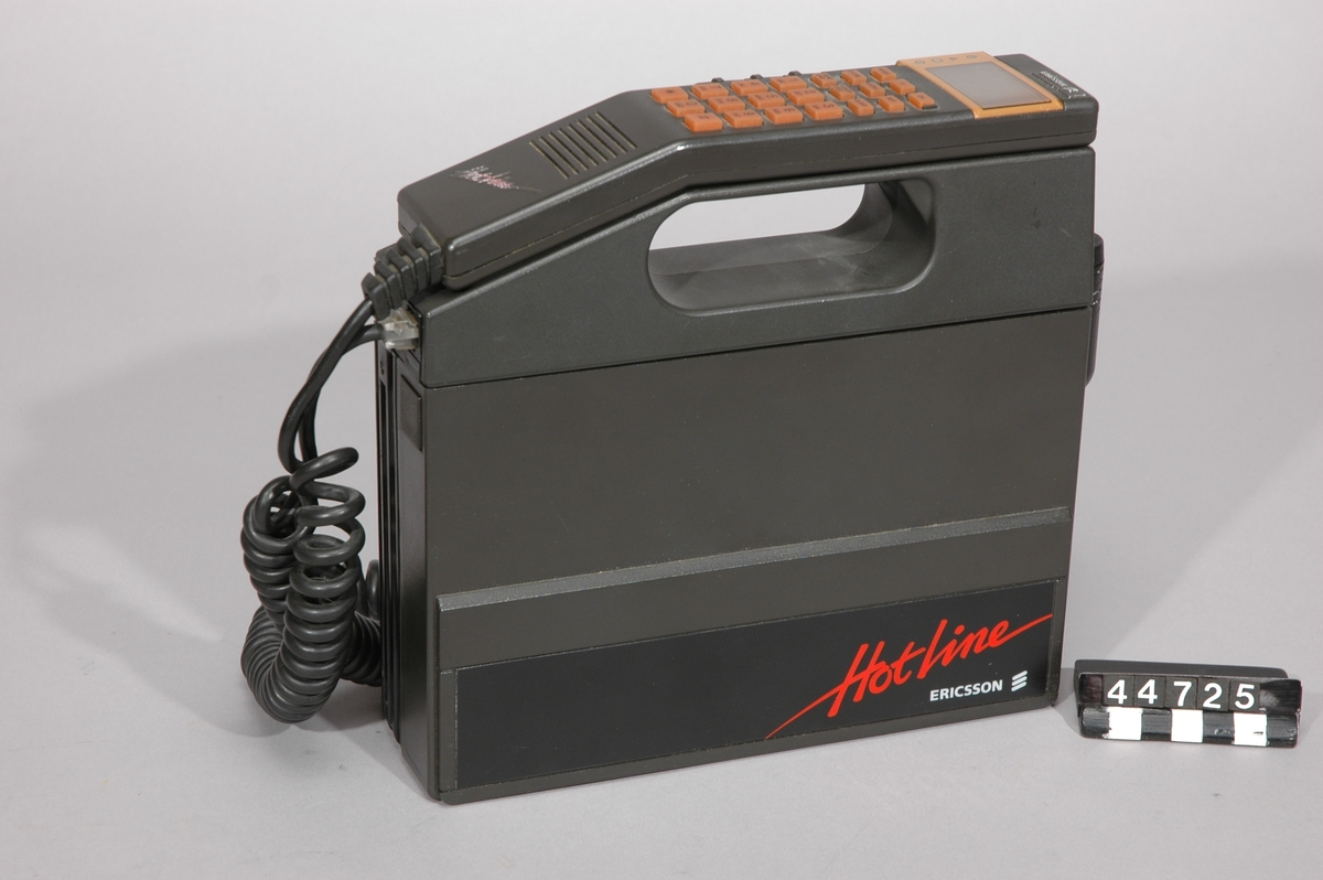 Mobiltelefon i väskmodell för NMT 450-nät typ Hotline Combi.  Telefondelen märkt:Code-KRC 101 1001/A R5A, typ-911 D,sernr 8100045. Toppdelen innanför batteriet: Code-SXK 107 103/2 R1A, typ-4101B, sernr-7480072. Batteriet-Ericsson, typ 3501, S/N 3050054, BKB 191 04/1 R1B Telefonluren: Code-KRD 101 1001/5A R1A, typ-2101 B, sernr-8030593.